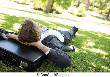Businessman resting head on briefca