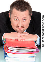 Businessman resting head on piles of paperwork