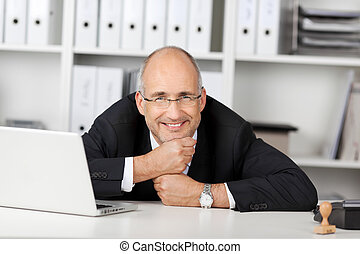 Businessman Resting His Chin On Fists At Office Desk