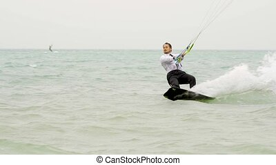 businessman rides a kite in the tropical ocean and performs...