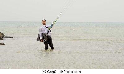 businessman rides a kite in the tropical ocean