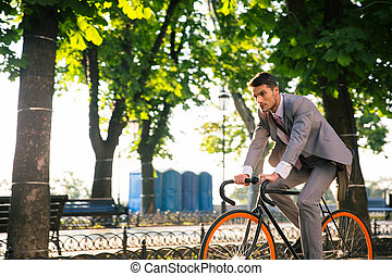 Businessman riding bicycle to work in park in morning