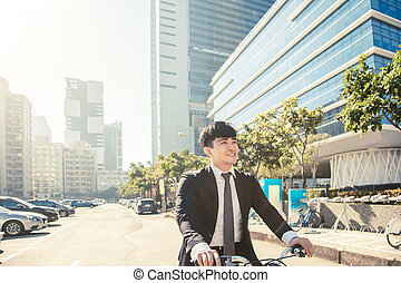 Businessman riding bicycle to work on urban street at morning