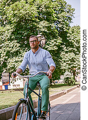 Businessman riding bicycle to work on urban street in morning.
