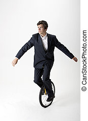 Businessman riding unicycle