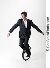 Businessman riding unicycle