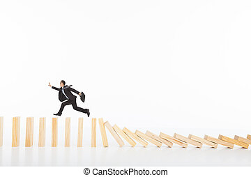 businessman running and catching on toppling dominoes