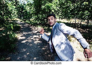 Scary businessman running away from something outdoors in park