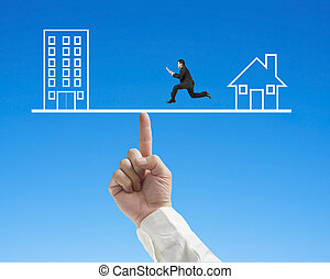 Businessman running on seesaw with Office and home drawing -...