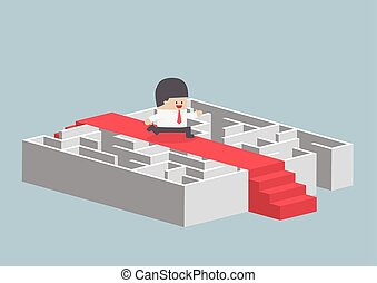 Businessman running on the red carpet over the maze