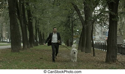 Businessman running with big white dog in alley of green trees, autumn