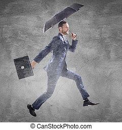 Businessman running with umbrella and briefcase.
