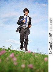 businessman runs on grass