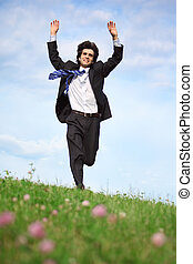 businessman runs on grass with lifted hands