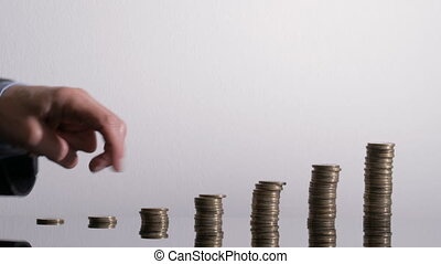 Businessman´s hand takes a walk over the coin stacks