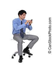 Businessman sat on chair sending SMS