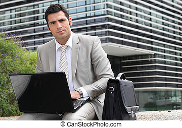 Businessman sat outside with laptop computer
