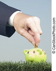 businessman saving money on a piggy-bank