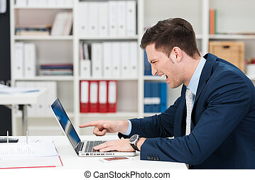 Businessman screaming and pointing at his laptop