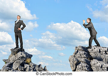 Businessman screaming and standing on the mountain
