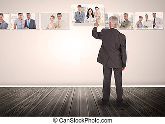 Businessman selecting business people digital interface