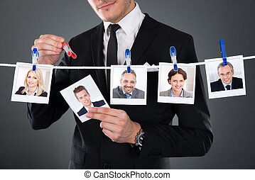 Businessman Selecting Candidate From Clothesline - ...