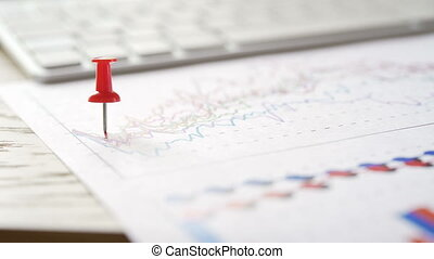 Businessman sets multicolored pins on the financial report graph