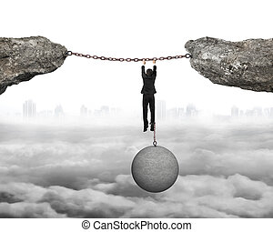 Businessman shackled by heavy concrete ball hanging on iron chains connected two cliffs with cloudy cityscape background