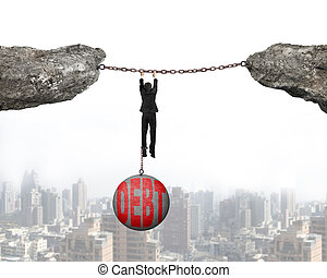 Businessman shackled by debt concrete ball hanging on iron chains connected two cliffs with urban scene background