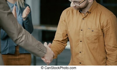 Businessman shake hands. Group of people clapping on a background. Team congratulates with conclusion of the contract.