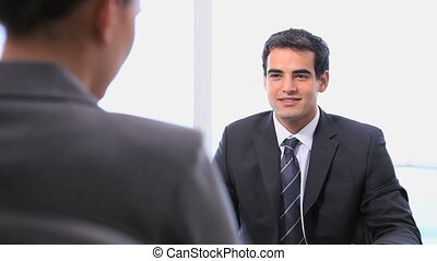 Businessman shakes hands with a businesswoman in his office