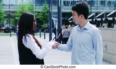 Businessman shaking businesswoman's hand in a sign of an agreement