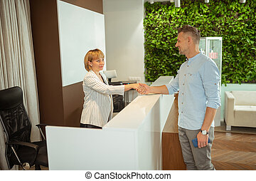 Businessman shaking hand of administrator while coming to