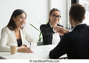 Businessman shaking hand of female coworker during company meeti