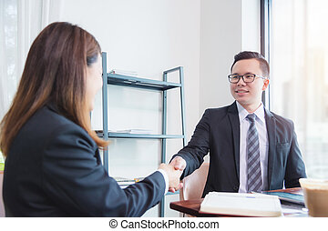 Businessman shaking hand with businesswoman in office