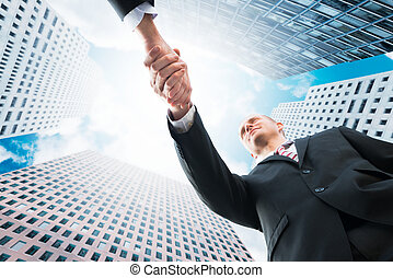 Businessman Shaking Hand With Partner Against Office Buildings