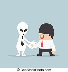 Businessman shaking hands with Alien