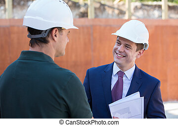 Businessman Shaking Hands With Builder On Construction Site