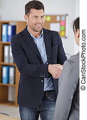 businessman shaking hands with client in office