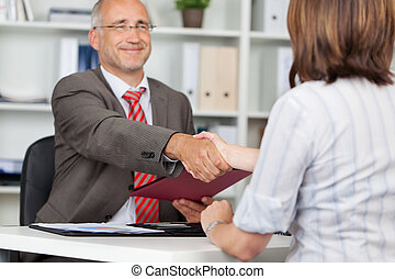 Businessman Shaking Hands With Female Candidate - Mature ...