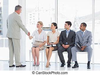 Businessman shaking hands with woman besides people waiting...