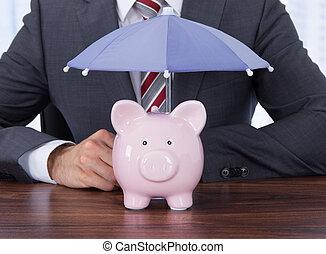 Businessman Sheltering Piggybank With Umbrella At Desk - ...