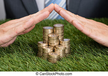 Businessman Shielding Stacked Coins On Grass
