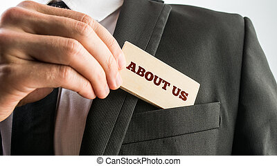 Businessman showing a wooden card reading - About us - as he...