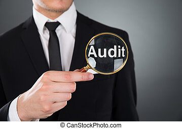 Businessman Showing Audit Word Through Magnifying Glass -...