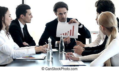 Businessman showing diagram report at meeting in office