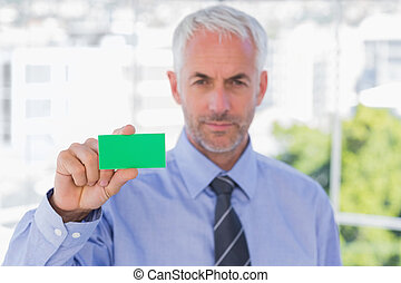 Businessman showing green business card