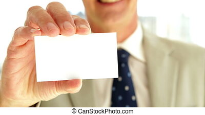Businessman showing his card to camera in his office