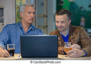 businessman showing his co-worker information in a computer