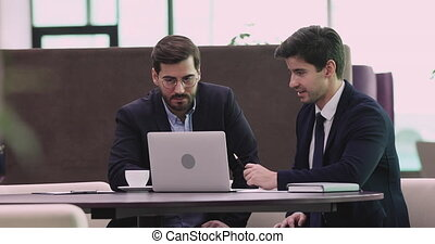 Young businessman executive financial investment advisor wear suit showing presentation on laptop consulting business investor client about software trading shares data sit at office table meeting